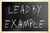 """Lead by example"" handwritten with white chalk on a blackboard — Stockfoto"