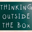 Thinking outside the box phrase, handwritten with white chalk on — Stock Photo