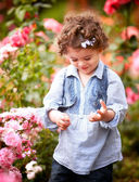 Baby girl in rose garden — Stock Photo