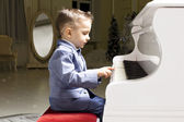 Little boy in a suit playing the piano — Foto Stock