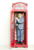 Little boy in English red phone — Stock Photo