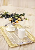 Tray with morning coffee in a bed decorated with roses — Stock Photo