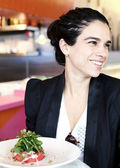 Beautiful woman in a restaurant eating — Stock Photo