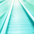 Perspective wide angle view of modern light blue illuminated and spacious high-speed moving commercial escalator with fast blurred trail of handrail in vanishing traffic motion in airport corridor — Stock Photo