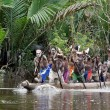 Asmat men paddling in their dugout canoe — Stock Photo