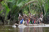 Asmat men paddling in their dugout canoe — Stockfoto