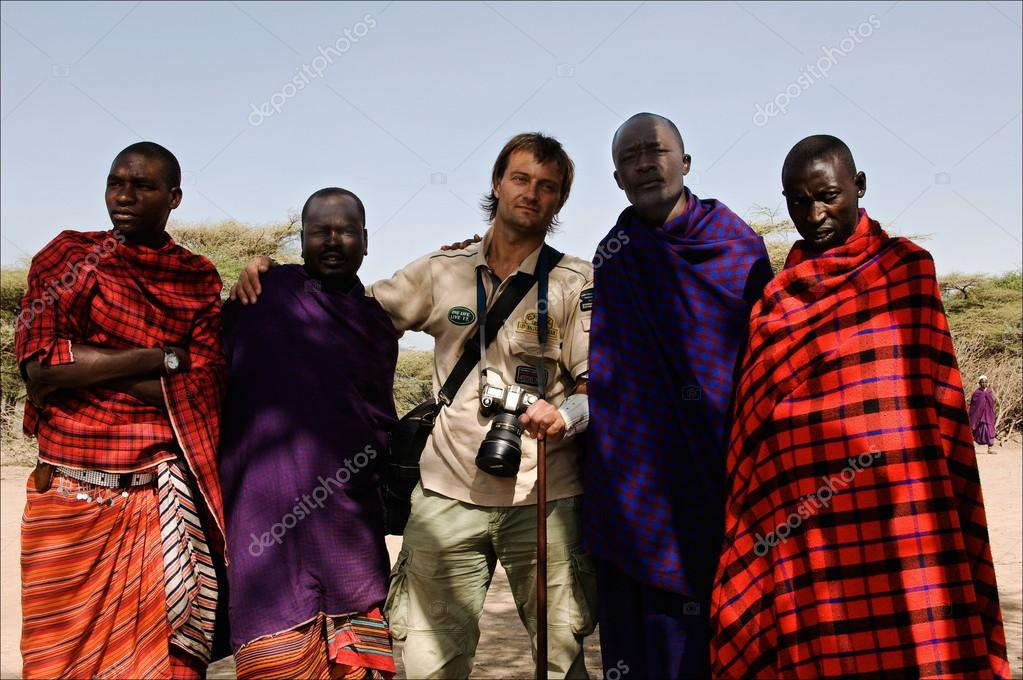 MASAI MARA,TANZANIA, - MARCH 5: Photographer Sergey Uryadnikov on a visit at Massai. Massai in traditional clothes welcome the guest. The Maasai (also Masai).  5 March 2009 In Maasai village, Africa, Tanzania.   Stock Photo #14551739