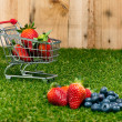 Blueberries and Strawberries in a shopping cart — Stock Photo
