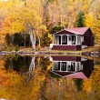 Reflections of a autumn forest and a house in a lake — Stock Photo