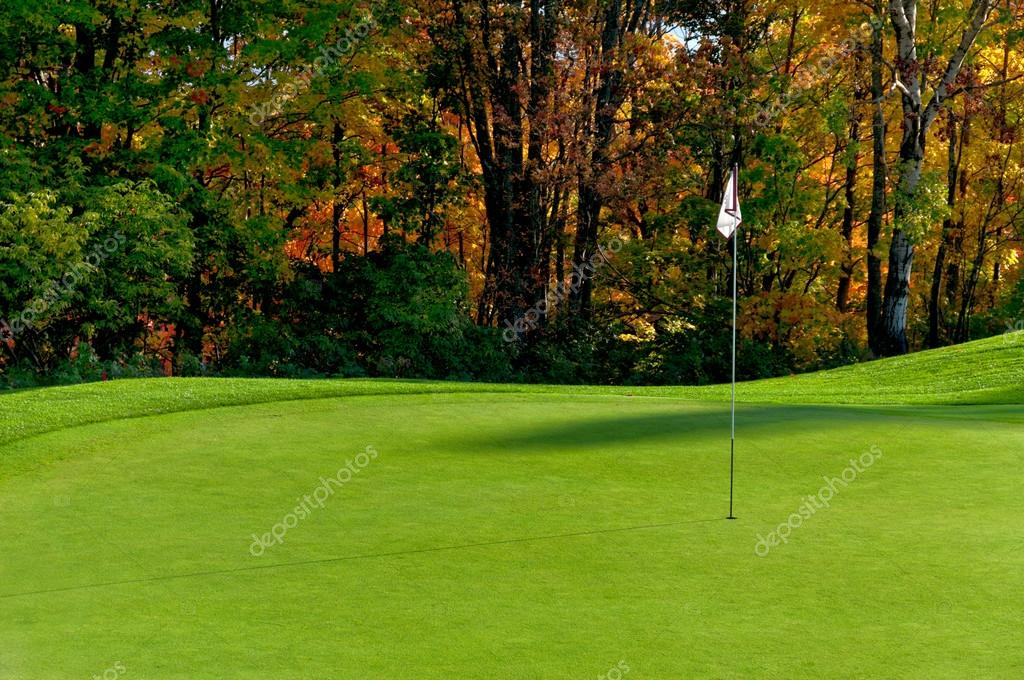 Golf course putting green with flag in autumn colors — Stock Photo #17183151