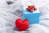 Caja de regalo azul con lazo rojo en velo de novia — Foto de Stock