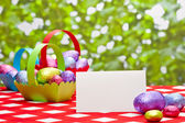 Easter eggs with place card and baskets — Stock Photo