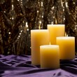 Four candles over purple velvet — Stock Photo