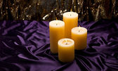 Four candles over purple velvet — Zdjęcie stockowe