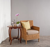 Rattan chair in lounge setting — Stok fotoğraf