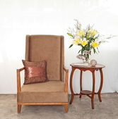 Beige upholstered chair with side table — Stock fotografie