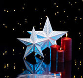 Backlit stars in blue with red candles — Stock Photo