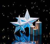 Backlit stars in blue with silver candles — Stock Photo