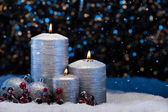 Three Silver Candles in snow  — Stock Photo