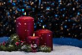 雪の中で 3 つの赤い蝋燭 — ストック写真