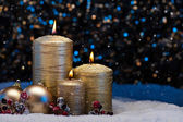 Three Gold Candles in snow  — Stock Photo