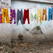 Stock Photo: Colorful kid`s pants are drying after laudry on the street