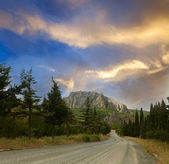 Rural road in mountain and the blue sky — Stock Photo