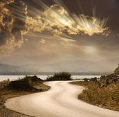 Strada del serpente sotto un cielo drammatico con raggi di sole — Foto Stock