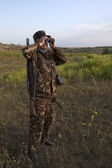 双眼鏡で見ている銃を持つ男 — ストック写真