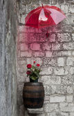 Wooden barrel with floers under the umbrella — Stock Photo