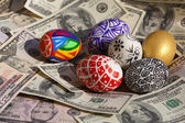 Colorful eggs on money background — Stock Photo