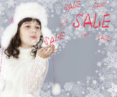 Winter sale cute girl blow to snowflakes — Stock Photo