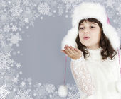 Cute girl white dressing blow snowflakes — Stock Photo