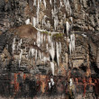 Melting cascade of icicles on a cliff face — Stock Photo