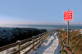 Warning sign on a winter snow cliff walk — Stock fotografie
