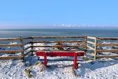 Seasonal snow covered red bench sea view — Stock Photo