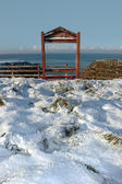 Seasonal snowy frost covered framed red bench sea view — Foto Stock