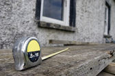 Builders diy tape measure on scaffolding at building site — Stock Photo