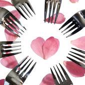 Garfos circundantes a forma do coração e pétalas de rosa — Fotografia Stock