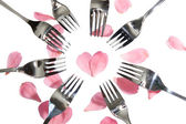 Forks surrounding heart shape with rose petals — Stock Photo
