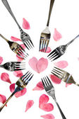 Silver and gold forks surrounding heart shape with rose petals — Stock Photo