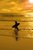 Silhouette of surfing couple walking from the sea — Stock Photo