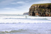 Lone surfer near cliffs — Stock Photo