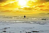 Man fishing among the waves — ストック写真