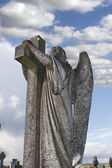 Angel statue embracing a cross — Stock Photo