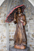 Wooden carved statue of Jesus holding an umbrella — Stock Photo