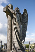 Angel statue embracing a cross and celtic graveyard — Stock Photo