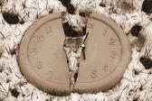 Broken clock face in the snow in sepia — Stock Photo
