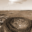 Sepia barbed wire on a rock with wind turbines — Stock Photo