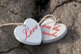 Love on the rocks wooden hearts — Stock Photo